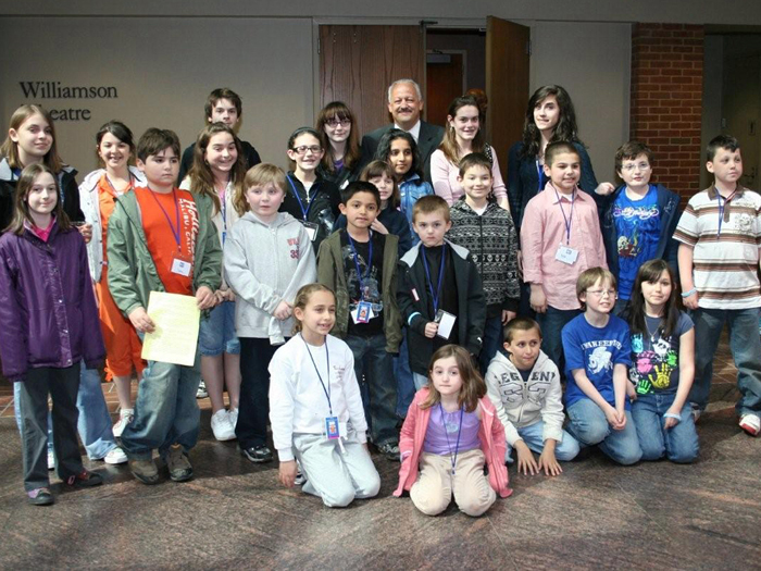 Children of CSI faculty and staff pose with President Dr. Tomás Morales in the Center for the Arts.