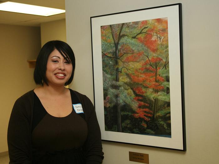 CSI student Emy-Luz Encarnacion poses next to Autumn Dusk in the new SEEK Program Art Gallery.